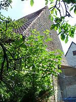 Südgiebel meit einem Teil der westlichen Dachfläche des nachbarlichen Scheunenteils (wegen Bäumen nur eingeschränkt sichtbar) / Ehem. Schafscheune in 74673  Mulfingen-Simprechtshausen (25.07.2018 - Bastian Heuberger)